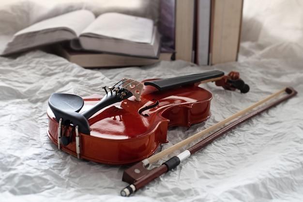 ぼやけた本の横に置かれた古典的なバイオリンと弓