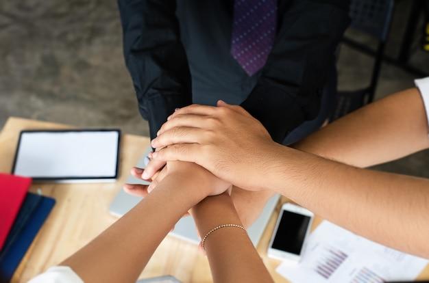 В селективном фокусе бизнес-группы руки сложены вместе