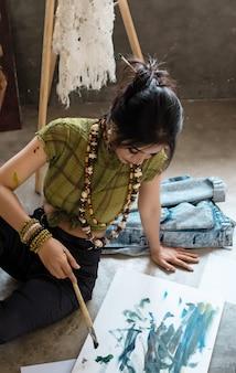 彼女のアートワークスタジオでアート絵画をやっている若いアーティスト