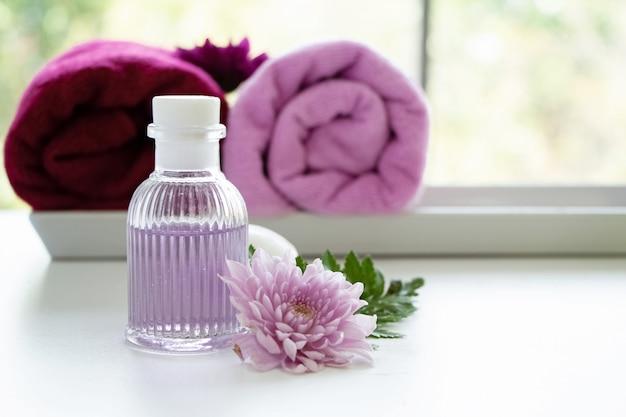 ピンクの花の横に置いたマッサージオイルの瓶
