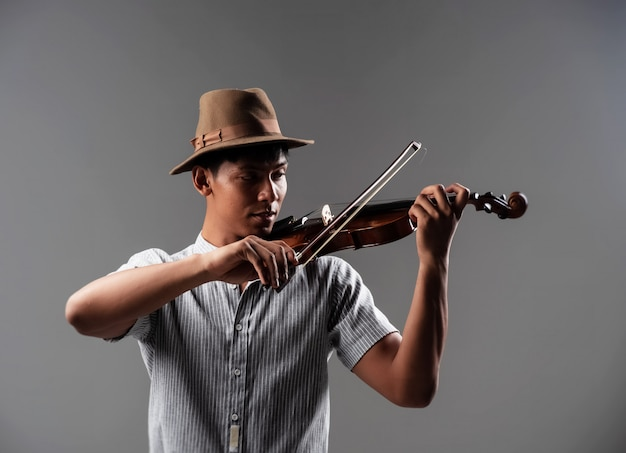 ハンサムな男が弦に弓をタッチしてバイオリンを弾く方法を見せる
