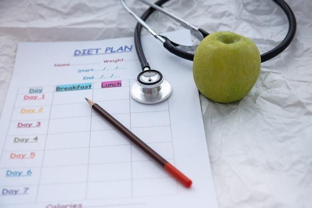 Стетоскоп и зеленое яблоко положить рядом с размытым планом графика диеты