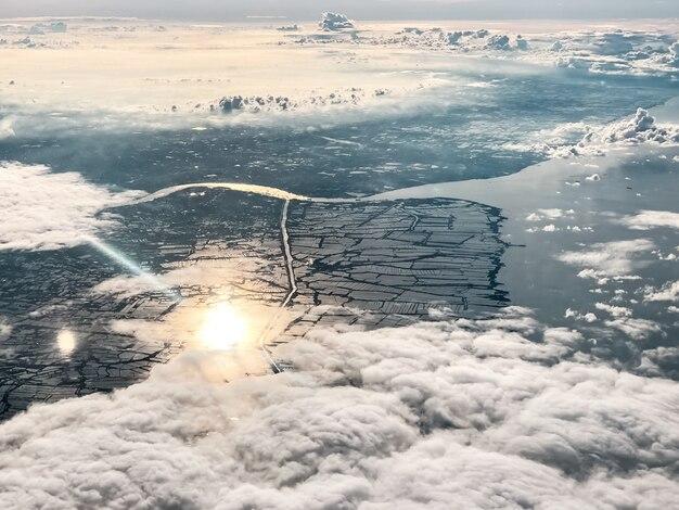 朝の空、街の上、たくさんの煙のような手を振る雲、周りを照らす日光の反射、自然の美しさ