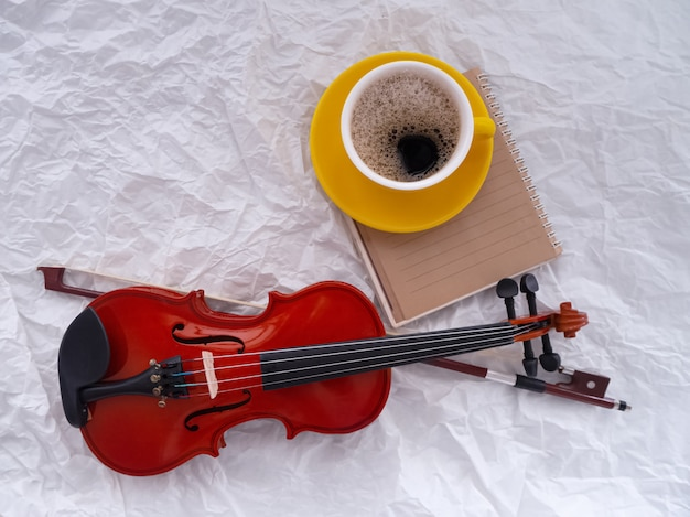 黄色のセラミックコーヒーカップの横に置かれた木製のバイオリン