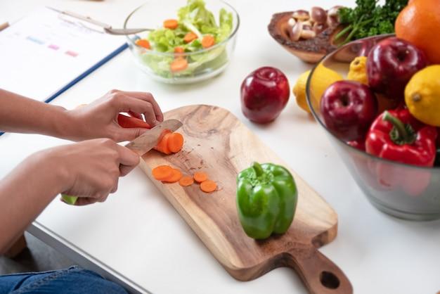 にんじんはナイフで切っていて、美容女性によるサラダの食事の準備をしていました。