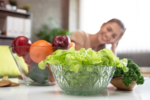 В селективном фокусе зеленых овощей в большой удар, перед затуманенное красивая женщина