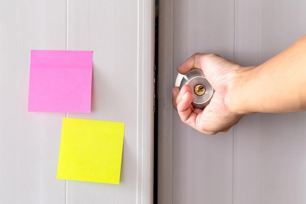 金属製のドアノブ付きの抽象的な白いドアは、ロックされ、ドアの上にステッカーの紙のメモです。