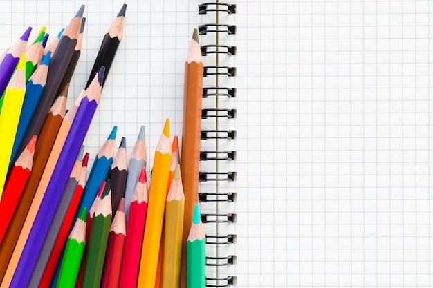 教育概念の背景。紙の本にクレヨンやパステル