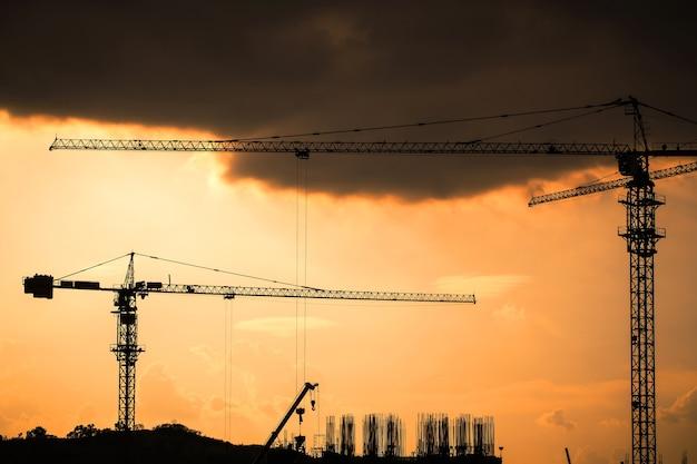 工業用建設用クレーンおよび建物のシルエット。
