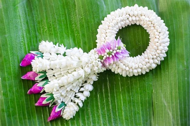 バナナの葉の背景に花のジャスミンの花輪。