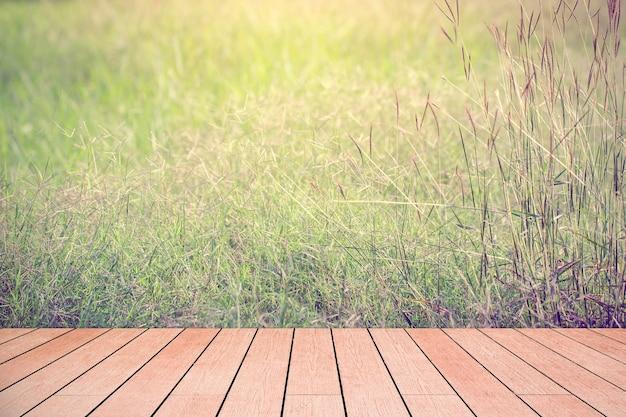 太陽の背景の草原の抽象的な木のテーブルトップ。