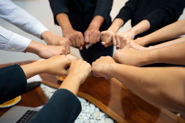 若いグループは、チームワーク、成功、コンセプトのための団結とライン接続への手を象徴する、仕事の成功、手を動かすための手を組んでいます。