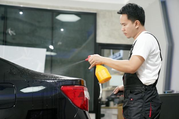 車のラッピングのスペシャリストは、ビニールフォイルまたはフィルムを黒い車に貼り付けて保護フィルムを矯正します。