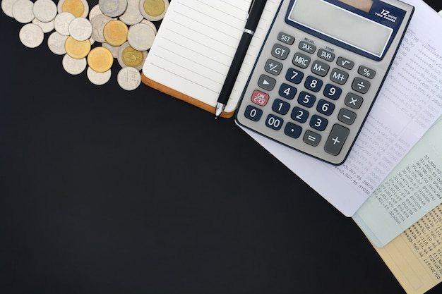 口座、電卓、メモ帳、および黒い背景にコインの山を保存する通帳のトップビュー