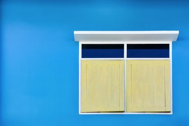 青いセメント壁の背景に分離された白い日除けと黄色のシンプルなビンテージウィンドウ