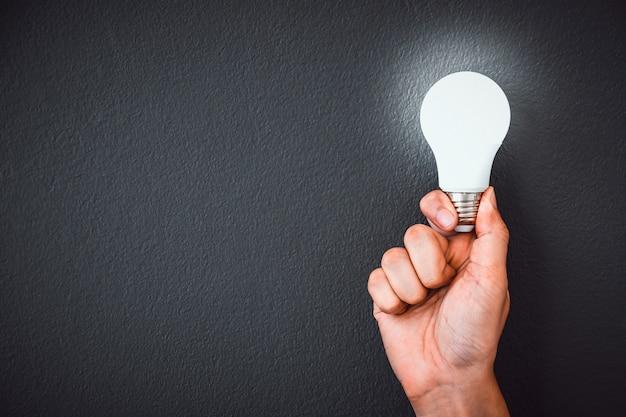 Мужская рука держит светодиодную лампочку над черной стеной