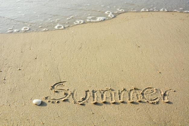 Надпись «лето», пишущая на песке на берегу моря