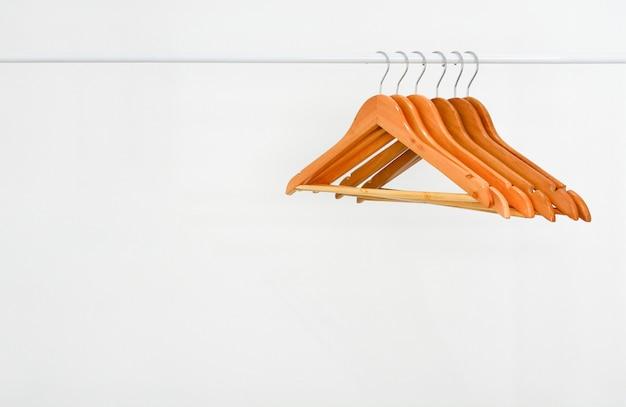 白い背景の上のホワイトメタルの洋服棚に空の木製ハンガーの行