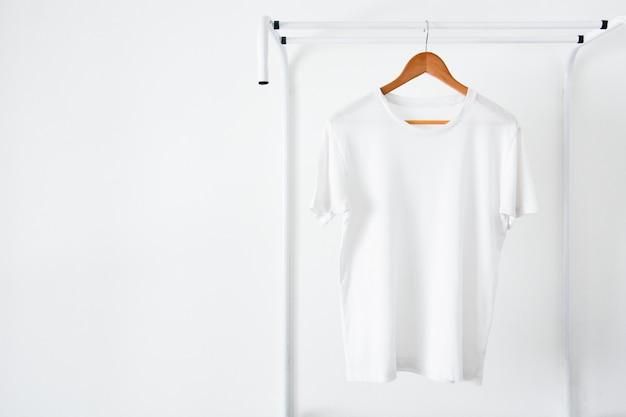 Белая футболка висит на деревянной вешалке