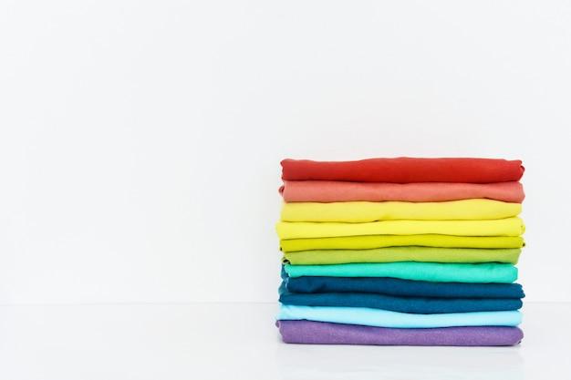 Стек красочные футболки на белом фоне