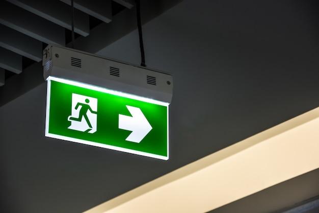 Загоренный зеленый знак аварийного выхода вися на потолке в современном здании