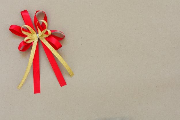 茶色の紙の背景の隅に赤と金のサテンの弓のリボン