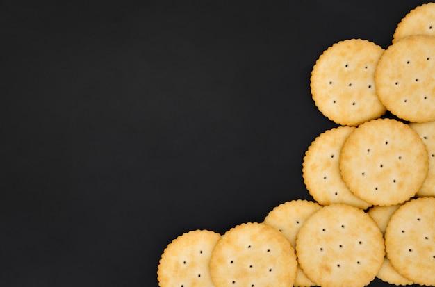 黒い色の背景に砂糖と丸いチーズクラッカークッキーのトップビュースタック