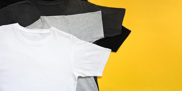 Вид сверху черная, серо-белая цветная футболка на желтом фоне