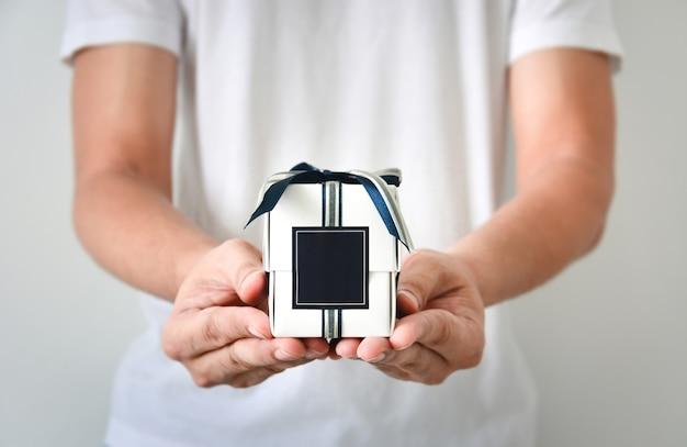 Мужские руки держат маленькую белую подарочную коробку, обернутую сине-серебряной цветной лентой и темно-синей пустой этикеткой