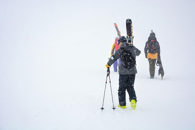 Мужской лыжник несет лыжи и снаряжение к трассе на склоне горы во время снегопада в зимний день
