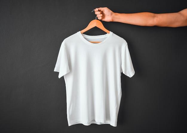 Закройте руки, держащей белая футболка висит на деревянной тканевой вешалке