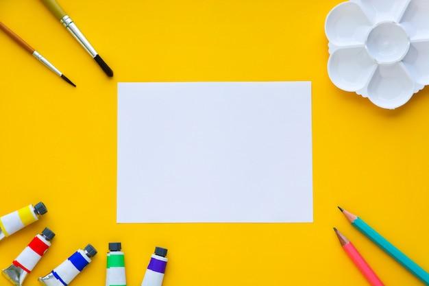 Вид сверху кистей, цветных трубок, карандашей, палитры и белой бумаги