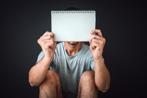 Человек сидит на полу с пустой записной книжкой