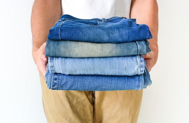 Закройте стопку сложенных джинсовых синих джинсов в руке на фоне стены белого цвета