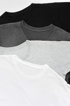 Вид сверху стопка чёрной, серо-белой (монохромной) футболки