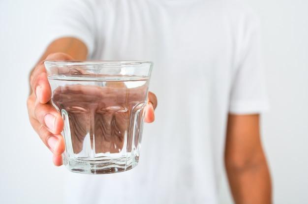 白い背景にきれいな水のガラスを持っている人間の手