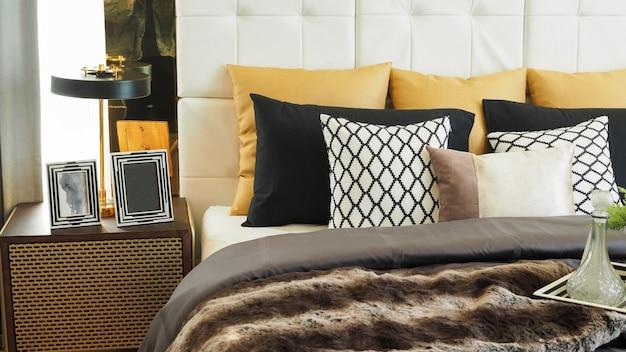 ベッドの上に白、ベージュの茶色と黒の色調の枕とクッション