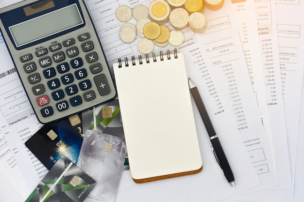 Вид сверху кредитных карт с выписками, ручкой, пустым блокнотом, стопкой монет и калькулятором