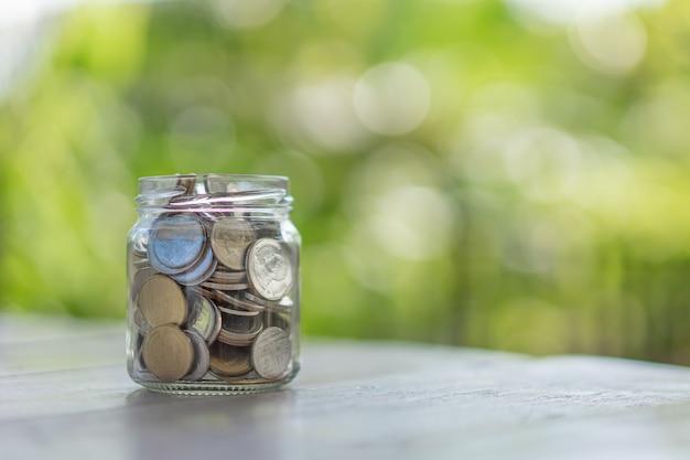 ガラスジャー、ビジネス、金融、貯蓄または管理のお金のコインのスタックのクローズアップ