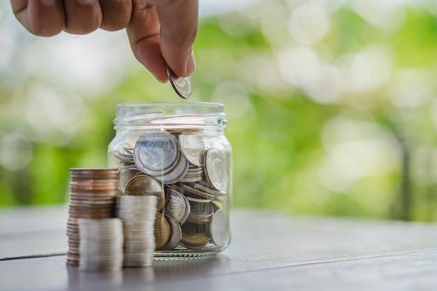 Рука кладет монеты в стеклянную банку, бизнес, финансы, сбережения или деньги управления