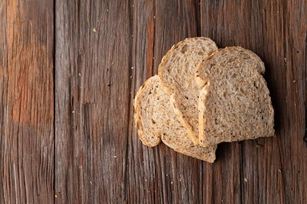 全粒小麦、暗い木の板に全粒粉パン、クローズアップ、トップビュー