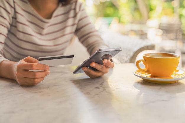 Макрофотография женщина с помощью кредитной или дебетовой карты с помощью приложения на смартфоне для оплаты онлайн
