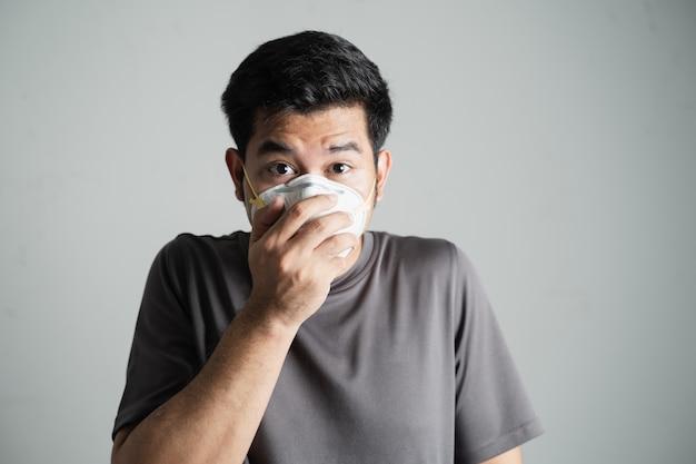 アジアの若い男が彼の鼻をかむ