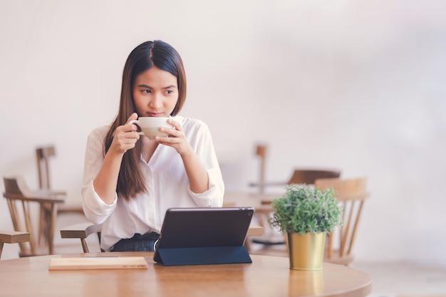 アジアの女性はコーヒーラテを飲んでいます