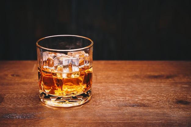 黒い背景に木製のテーブルの上のアイスキューブとウイスキーのグラス