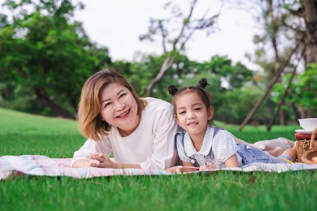 アジアの祖母と孫娘の屋外の緑のガラス畑の上に敷設、夏の日に一緒にピクニックを楽しむ家族