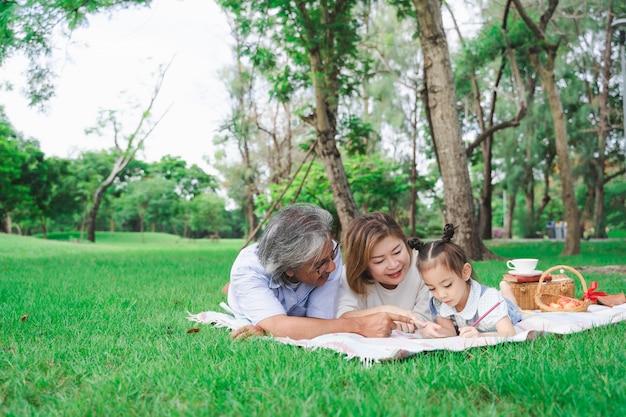 アジアの祖父母と孫娘の屋外の緑のガラス畑の上に敷設、夏の日の概念で一緒にピクニックを楽しむ家族の肖像画