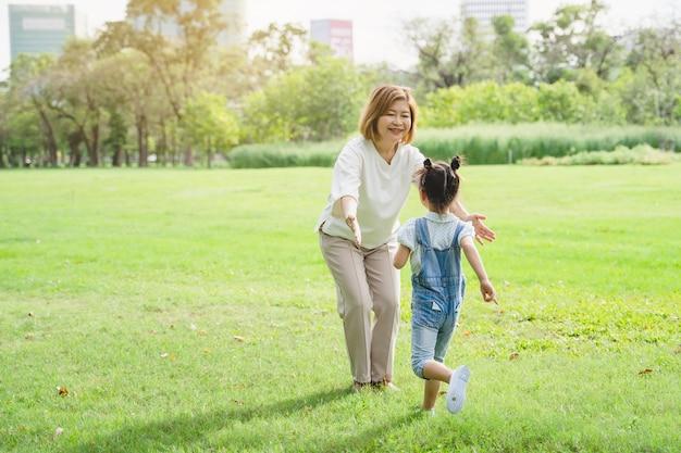 アジアの祖母と孫が公園で一緒に幸せな時間を過ごして