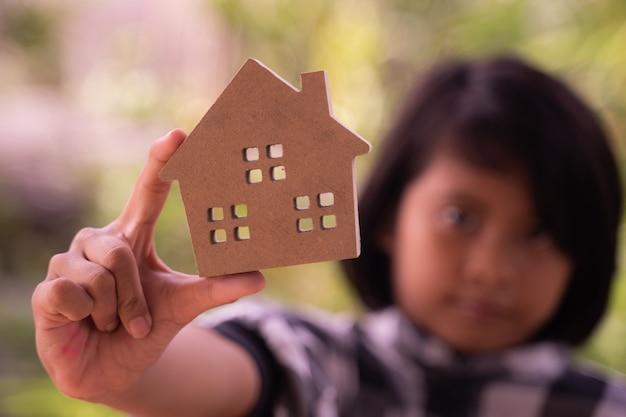 女の子の手で木製のおもちゃの家を閉じます