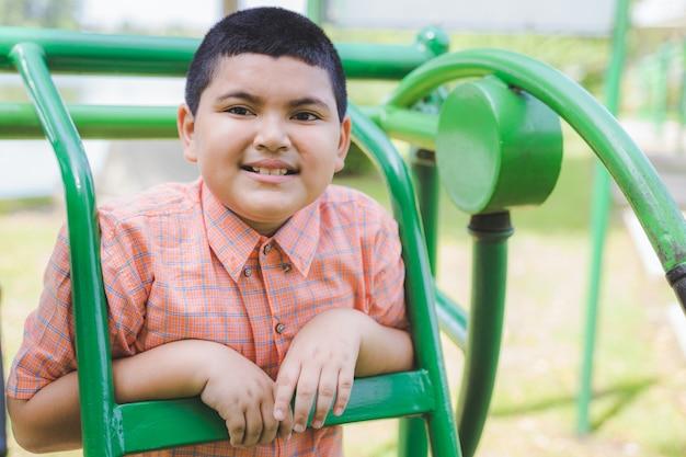遊び場で遊んで、カメラに笑顔かわいい太ったアジアの少年の肖像